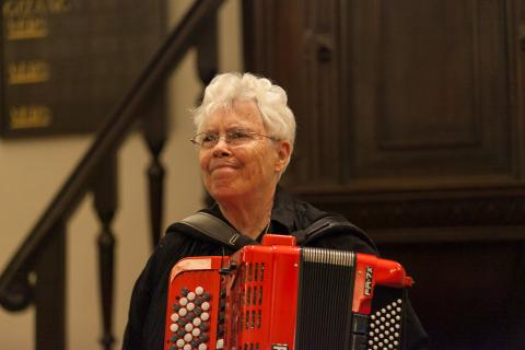 Pauline Oliveros holding a red accordion