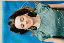 woman laying on a yoga mat with ear buds